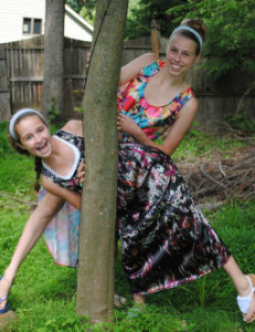 2 girls peaking out from a tree wearing dresses they made
