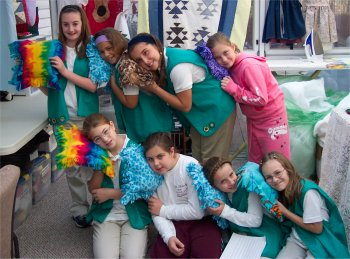 a group of girl scouts showing their projects they sewed for their sewing badge.