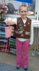 a little girl who is a brownie showing her fabric windsock she made to get her sewing badge