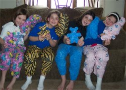 4 girls in pajama pants and holding a pillow and a teddy bear