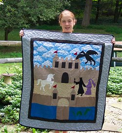 a teen holding a quilt they made of a castle, princess, and unicorn