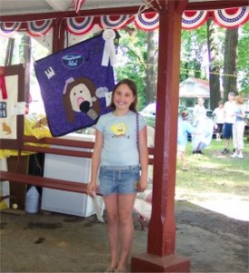 girl standing next to a quilt she made with an award