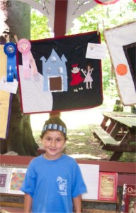 little girl standing next to a quilt she made with an award