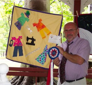 a man standing next to a quilt a kid made with an award