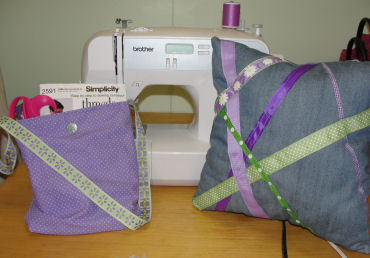handmade purple ribbon pillow and lined shoulder bag sitting next to a sewing machine