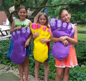 little girls holding a giant foot pillow with toe nails that they sewed